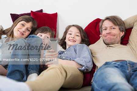 Family lying on couch, smiling Stock Photo - Premium Royalty-Free, Image code: 6121-07740954