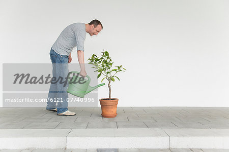 Mature man watering little tree Stock Photo - Premium Royalty-Free, Image code: 6121-07740996