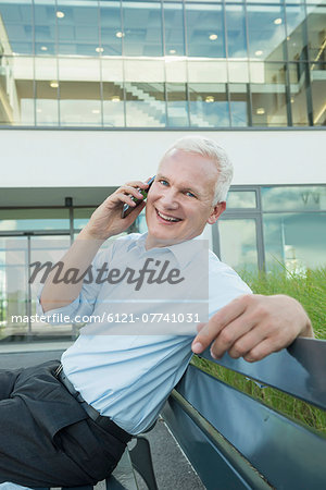portrait of businessman sitting on a bench using his smartphone Stock Photo - Premium Royalty-Free, Image code: 6121-07741031