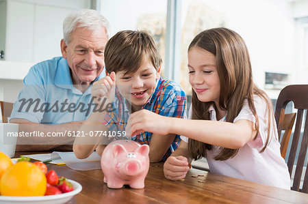 Two children and grandfather with piggy bank Stock Photo - Premium Royalty-Free, Image code: 6121-07741059
