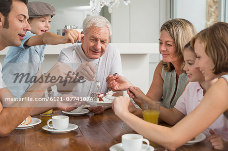 Extended family at table eating cake Stock Photo - Premium Royalty-Free, Image code: 6121-07741074