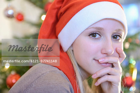 Portrait of teenage girl in front of christmas tree Stock Photo - Premium Royalty-Free, Image code: 6121-07741148