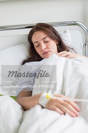 Patient in hospital lying in bed Stock Photo - Premium Royalty-Free, Image code: 6121-07741172
