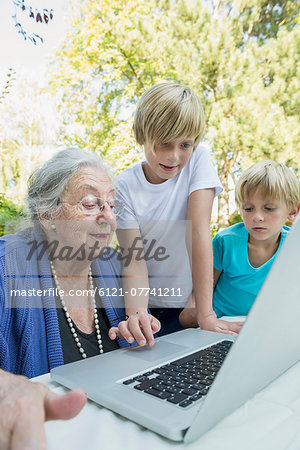 Grandmother and her two grandsons looking at laptop Stock Photo - Premium Royalty-Free, Image code: 6121-07741211