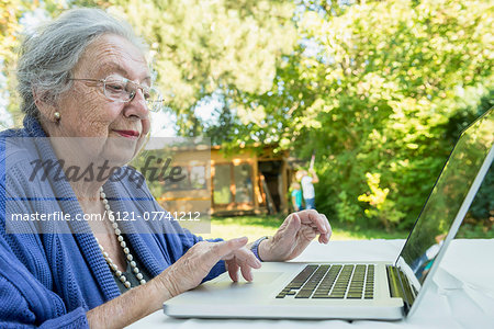 Female senior using laptop Stock Photo - Premium Royalty-Free, Image code: 6121-07741212