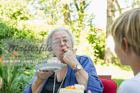Grandmother eating cream cake with her grandson Stock Photo - Premium Royalty-Free, Image code: 6121-07741216