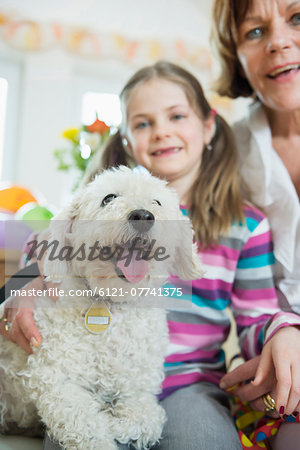 Portrait of grandmother and grandchild with dog in living room, smiling Stock Photo - Premium Royalty-Free, Image code: 6121-07741375