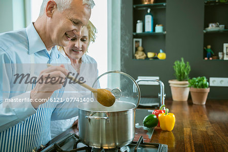 Mature couple preparing food in kitchen, smiling Stock Photo - Premium Royalty-Free, Image code: 6121-07741400