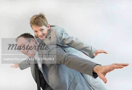 Father giving piggy back ride to his son, smiling Stock Photo - Premium Royalty-Free, Image code: 6121-07741402
