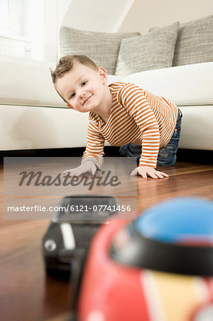Portrait of boy playing with toys, smiling Stock Photo - Premium Royalty-Free, Image code: 6121-07741456