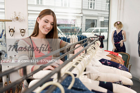Young woman shopping in fashion store, smiling Stock Photo - Premium Royalty-Free, Image code: 6121-07741470