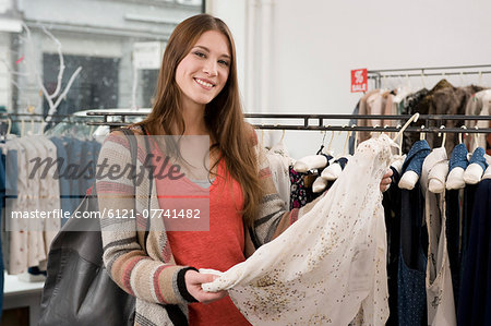 Portrait of young woman shopping in fashion store, smiling Stock Photo - Premium Royalty-Free, Image code: 6121-07741482
