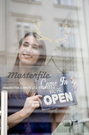 Sales girl holding opening board of fashion shop, smiling Stock Photo - Premium Royalty-Free, Image code: 6121-07741504