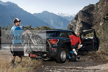 Men taking mountainbikes off car, Italy Stock Photo - Premium Royalty-Free, Image code: 6121-07741515