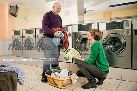 Young woman is helping to senior man in laundry Stock Photo - Premium Royalty-Free, Image code: 6121-07741579