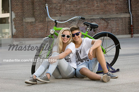 Teenage couple sitting on street with bicycle, smiling Stock Photo - Premium Royalty-Free, Image code: 6121-07741606