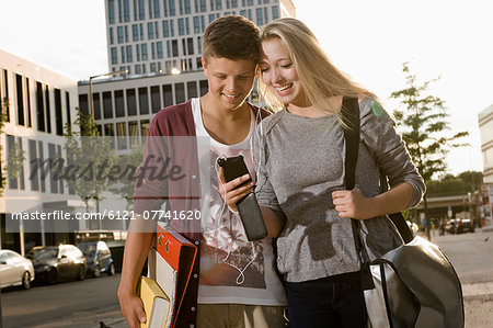Teenage couple listening music with smart phone, smiling Stock Photo - Premium Royalty-Free, Image code: 6121-07741620