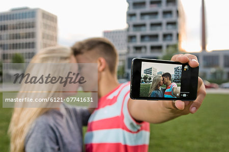 Teenage couple taking self portrait with themselves Stock Photo - Premium Royalty-Free, Image code: 6121-07741631
