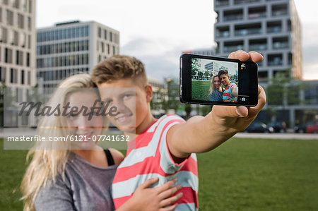 Portrait of teenage couple taking picture with smart phone, smiling Stock Photo - Premium Royalty-Free, Image code: 6121-07741632