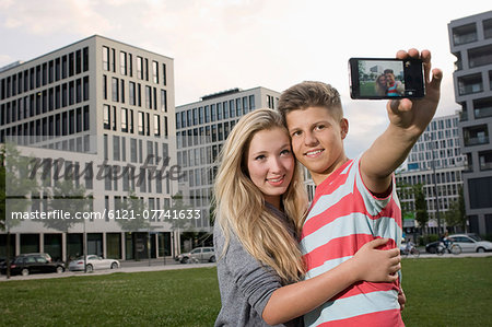 Portrait of teenage couple taking picture with smart phone, smiling Stock Photo - Premium Royalty-Free, Image code: 6121-07741633