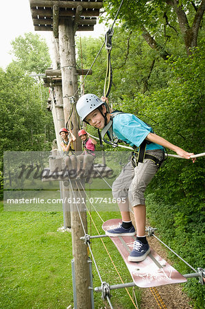 Boy and girls climbing crag, smiling Stock Photo - Premium Royalty-Free, Image code: 6121-07741695