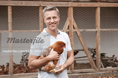 Farmer holding chicken on organic farm Stock Photo - Premium Royalty-Free, Image code: 6121-07741721