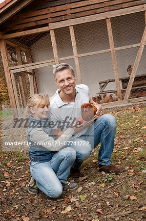 Father and daughter with chicken on organic farm Stock Photo - Premium Royalty-Free, Image code: 6121-07741722