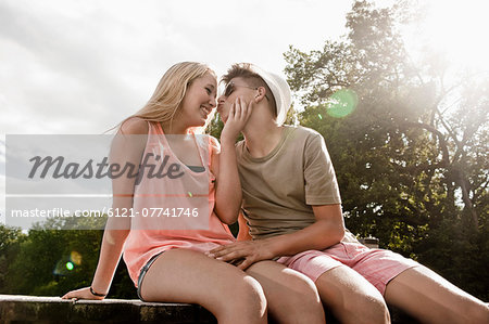 Teenage couple in love sitting on a jetty at lake Stock Photo - Premium Royalty-Free, Image code: 6121-07741746