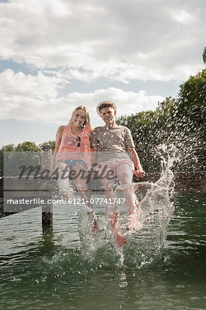 Teenage couple sitting on a jetty splashing water Stock Photo - Premium Royalty-Free, Image code: 6121-07741747
