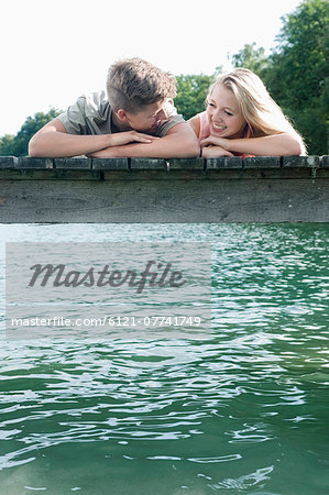 Teenage couple lying side by side on a jetty at lake Stock Photo - Premium Royalty-Free, Image code: 6121-07741749
