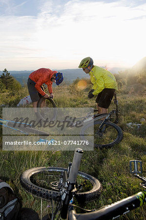 two mountain bikers repairing bicycle tyre, Vipava valley, Istria, Slovenia Stock Photo - Premium Royalty-Free, Image code: 6121-07741776