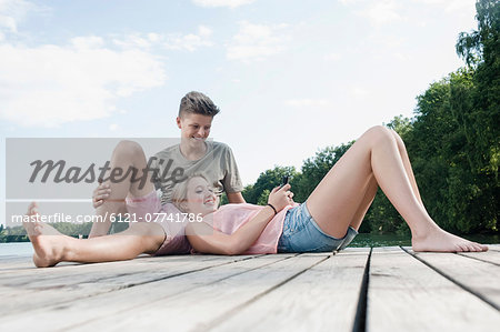 Teenage couple with smartphone relaxing on a jetty at lake Stock Photo - Premium Royalty-Free, Image code: 6121-07741786