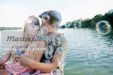 Teenage couple blowing soap bubbles on a jetty at lake Stock Photo - Premium Royalty-Free, Image code: 6121-07741789