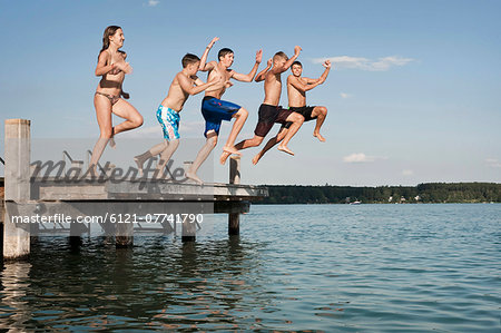 Five teenagers jumping from a jetty into lake Stock Photo - Premium Royalty-Free, Image code: 6121-07741790