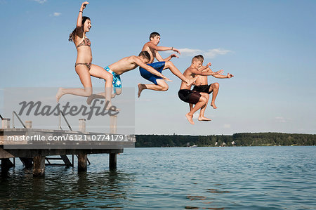 Five teenagers jumping from a jetty into lake Stock Photo - Premium Royalty-Free, Image code: 6121-07741791
