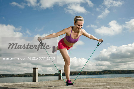 Woman woman exercising with resistance band, Woerthsee, Bavaria, Germany Stock Photo - Premium Royalty-Free, Image code: 6121-07741803