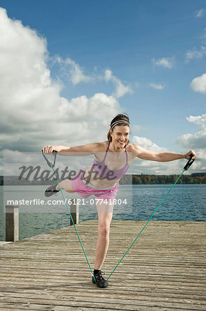 Woman woman exercising with resistance band, Woerthsee, Bavaria, Germany Stock Photo - Premium Royalty-Free, Image code: 6121-07741804