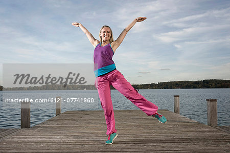 Woman dancing Zumba on jetty, Woerthsee, Bavaria, Germany Stock Photo - Premium Royalty-Free, Image code: 6121-07741860