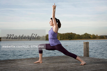 Woman practicing yoga on jetty, Woerthsee, Bavaria, Germany Stock Photo - Premium Royalty-Free, Image code: 6121-07741868