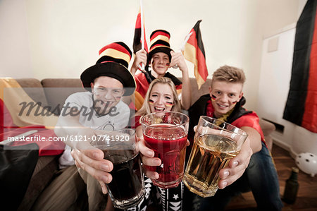 Teenage soccer fans toasting glasses Stock Photo - Premium Royalty-Free, Image code: 6121-07741920