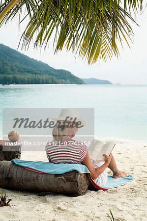 woman reading a book on the beach, Koh Lipe, Thailand Stock Photo - Premium Royalty-Free, Image code: 6121-07741952