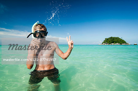 teenage boy with snorkeling equipment showing victory-sign, Koh Lipe, Thailand Stock Photo - Premium Royalty-Free, Image code: 6121-07741957
