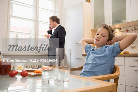 Bored boy in kitchen with father on the phone in background Stock Photo - Premium Royalty-Free, Image code: 6121-07809694