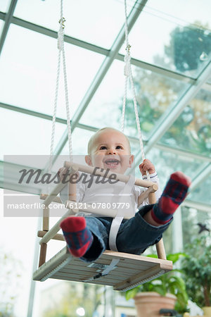 Portrait of laughing toddler sitting in a swing Stock Photo - Premium Royalty-Free, Image code: 6121-07809779