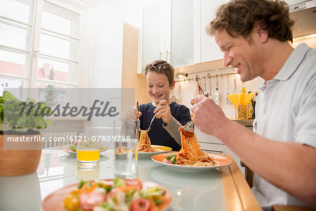 Father and son eating spaghetti and salad in kitchen Stock Photo - Premium Royalty-Free, Image code: 6121-07809798