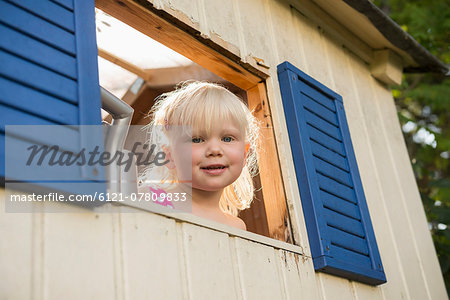 Smiling little girl looking out of tree house Stock Photo - Premium Royalty-Free, Image code: 6121-07809833