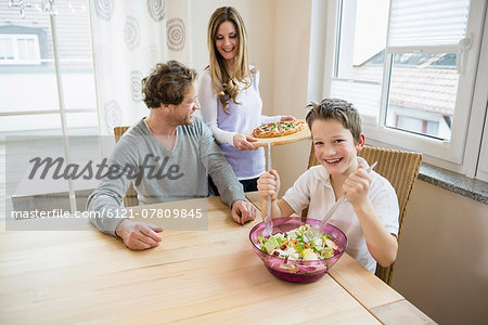 Family eating pizza and salad at home Stock Photo - Premium Royalty-Free, Image code: 6121-07809845