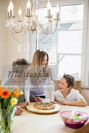 Family eating pizza and salad at home Stock Photo - Premium Royalty-Free, Image code: 6121-07809847