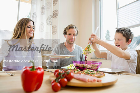 Family eating pizza and salad at home Stock Photo - Premium Royalty-Free, Image code: 6121-07809848