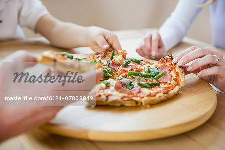 Family sharing a pizza Stock Photo - Premium Royalty-Free, Image code: 6121-07809849